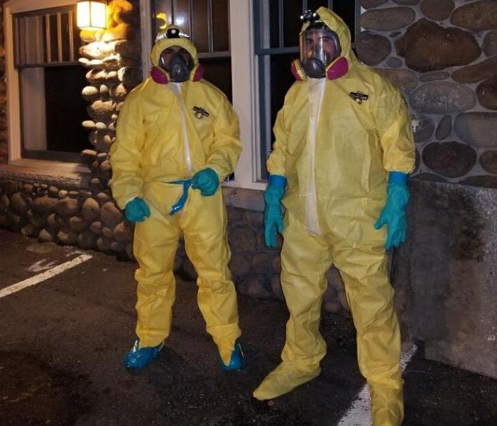 Two Men in Yellow Hazmat Suits Standing Outside of a Building