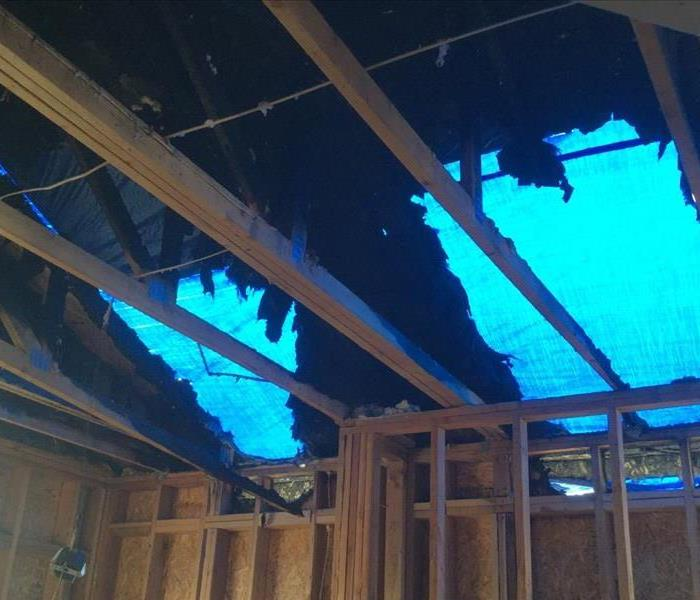 Fire Damage to a Roof with the Blue tarp covering roof shot from the inside of the fire damaged building
